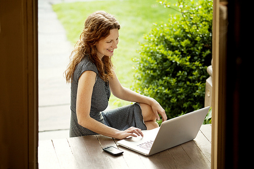woman with laptop on front porch