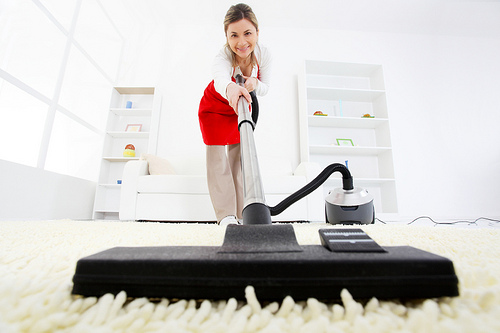 Cleaning lady vacuuming a soft carpet in living room.