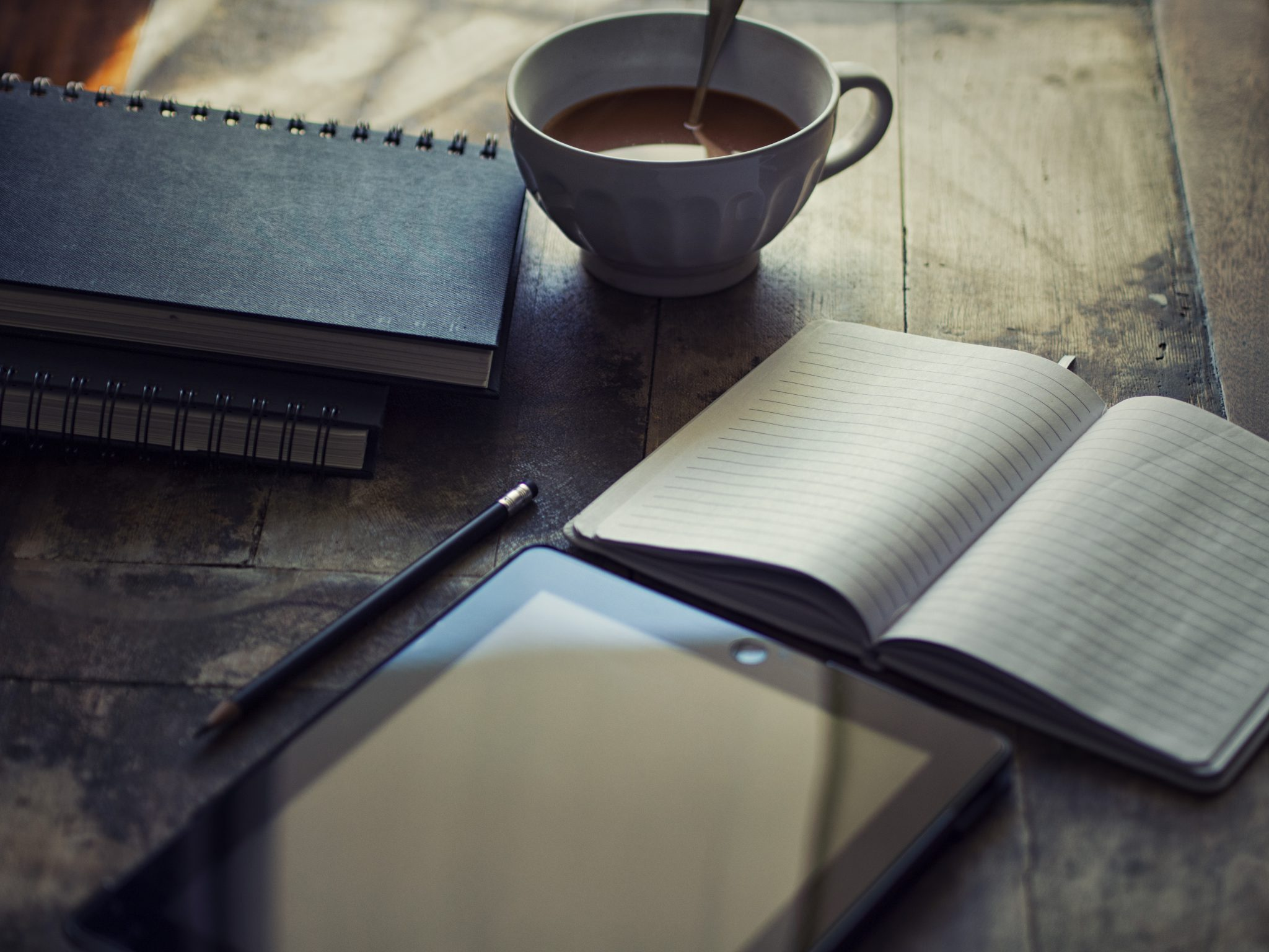 on a table: a tablet, a mug of coffee, and two journals
